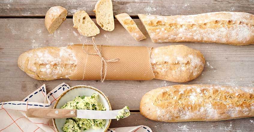 Baguettes auf dem Holztisch mit Kräuterbutter im Schälchen
