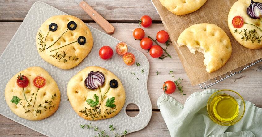 Focaccia Brote auf dem Brett und auf Toppits Backpapier