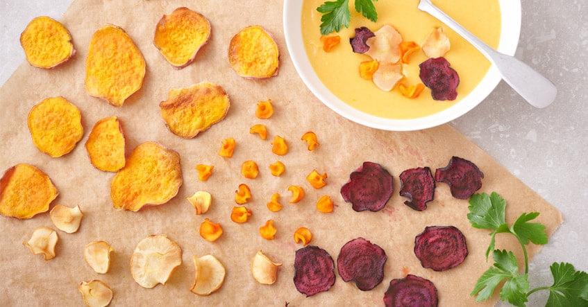 Gemüsechips von Pastinake, Süßkartoffel, Möhre und Rote Bete auf Backpapier, dazu Süßkartoffelsuppe in der Schale