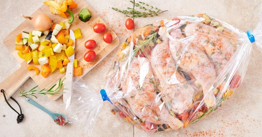 Hähnchenschenkel roh auf frischem Gemüse im Toppits Bratschlauch