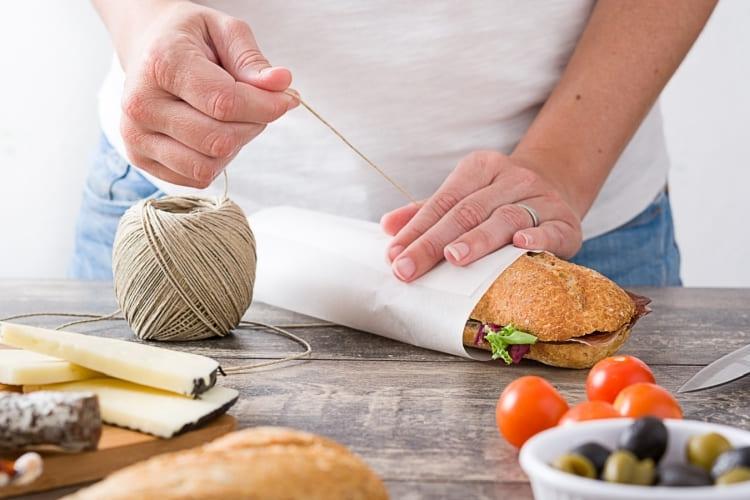 Sandwich wird in Butterbrotpapier eingewickelt.