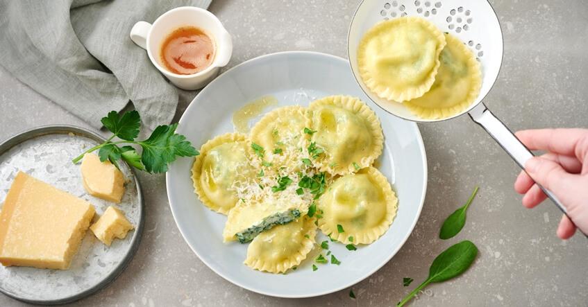 Spinat-Ricotta-Ravioli auf dem Teller und auf einem Schaumlöffel