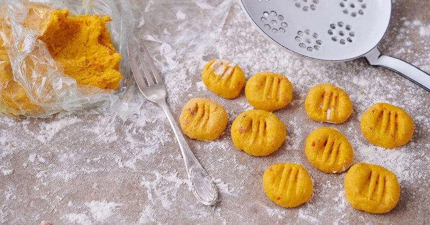 Teig für Kürbis-Gnocchi in Frischhaltefolie und rohe Gnocchi auf bemehlter Arbeitsfläche